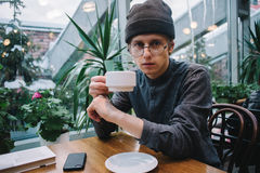 Young hipster student, went to have a cup of tea. lying on the table and phone book, and outside greenhouse with plants. Young hipster student in the cap on the Royalty Free Stock Image