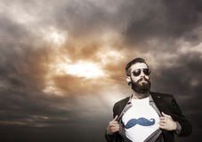 Young hipster superhero monitors under a dark sky Stock Photography