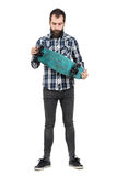 Young hipster in tartan shirt holding skateboard looking down Royalty Free Stock Images