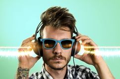 Young hipster tattooed man, listening to music. On , graphic sound waves added royalty free stock photography
