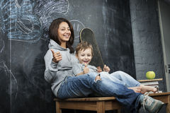 Young hipster teenage girl sitting with her brother in classroom multinational Stock Photography