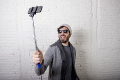 Young hipster trendy blogger man holding stick recording selfie video in vlog concept Royalty Free Stock Photos