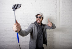 Young hipster trendy blogger man holding stick recording selfie video in vlog concept. Young attractive man in casual clothes beanie hipster style holding selfie Stock Images