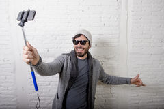 Young hipster trendy blogger man holding stick recording selfie video in vlog concept Stock Photos