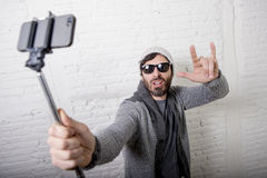 Young hipster trendy blogger man holding stick recording selfie video in vlog concept. Young attractive man in casual clothes beanie hipster style holding selfie Royalty Free Stock Photos