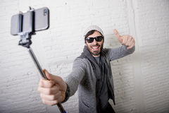 Young hipster trendy blogger man holding stick recording selfie video in vlog concept. Yoyoung attractive man in casual clothes beanie hipster style holding Royalty Free Stock Photos