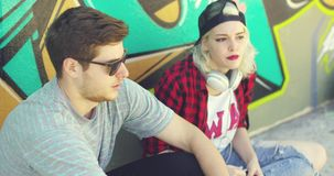 Young hipster urban couple relaxing on a sidewalk stock video