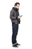 Young hipster wearing jacket over hooded sweatshirt typing on mobile phone. Royalty Free Stock Photo