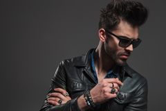 Young hipster wearing rings, sunglasses and leather jacket looks royalty free stock image