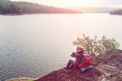 Young hipster woman with backpacker sitting on stone enjoying. Lake and mountain beautiful landscape view stock photo