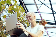 Young hipster woman with blonde short hair smiling and working on laptop, sitting on stairs. Indoor botanical garden interior. Royalty Free Stock Images