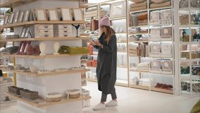 MINSK, BELARUS - OCTOBER 10, 2017. Inside Zara Home retail store in Minsk. A young hipster woman chooses home acessories stock image