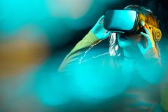 Young hipster woman with curly hair wearing virtual reality goggles and touch another world in studio neon lights. Smartphone using with VR headset stock image