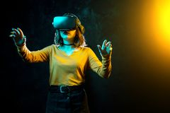 Young hipster woman with curly hair wearing virtual reality goggles and touch another world in studio neon lights. Smartphone using with VR headset royalty free stock photos