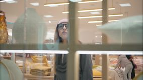 A young hipster woman in fashion glasses enters the store with showcases royalty free stock photography