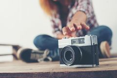 Young hipster woman hand reach out for catch retro camera. Young hipster woman hand reach out for catch retro camera background Stock Image