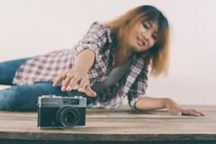Young hipster woman hand reach out for catch retro camera. Young hipster woman hand reach out for catch retro camera background Stock Photography