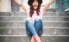Young hipster woman having fun throwing confetti with her hands - Happy pretty girl celebrating her gratuation sitting on stairs royalty free stock photography