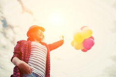 Young hipster woman holding balloons against sky.  Royalty Free Stock Photography