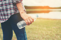 young hipster woman holding bottle of water at summer green park Stock Photos