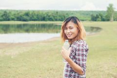Young hipster woman holding bottle of water at summer green park. Background Royalty Free Stock Photos