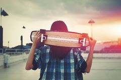 Young hipster woman holding skateboard behind head in cinematic Stock Photos
