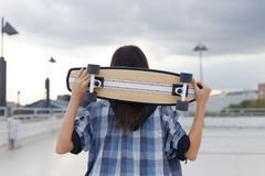 Young hipster woman holding skateboard behind head Stock Photos