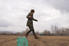 Young hipster woman jumping from a concrete block Stock Photos
