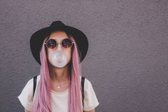 Young hipster woman with long pink hair blowing a bubble with bubble gum. stock photo