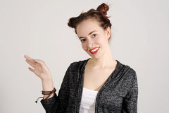 Young hipster woman is looking so kind into the camera with one hand up. Royalty Free Stock Photos