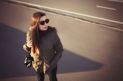 Young hipster woman in parka coat and sunglasses Stock Images