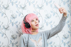 Young hipster woman in pink wig and dj headphones doing selfie against wall with vintage wallpapers pattern Stock Photos