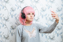 Young hipster woman in pink wig and dj headphones doing selfie against wall with vintage wallpapers pattern Stock Images