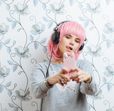 Young hipster woman in pink wig and dj headphones doing selfie against wall with vintage wallpapers pattern Stock Image