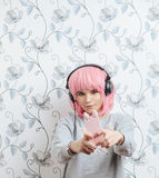 Young hipster woman in pink wig and dj headphones doing selfie against wall with vintage wallpapers pattern Royalty Free Stock Image