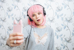 Young hipster woman in pink wig and dj headphones doing selfie against wall with vintage wallpapers pattern Stock Photo