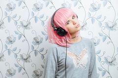 Young hipster woman in pink wig and dj headphones having fun against wall with vintage wallpapers pattern Royalty Free Stock Photography