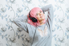 Young hipster woman in pink wig and dj headphones having fun against wall with vintage wallpapers pattern Royalty Free Stock Photos