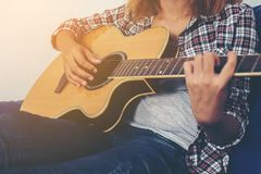 Young hipster woman playing a guitar. Young hipster woman playing a guitar background Royalty Free Stock Images