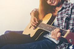 Young hipster woman playing a guitar. Young hipster woman playing a guitar background Stock Photography