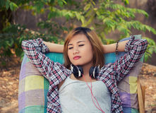 Young hipster woman relaxing in long chair with headphones on. Royalty Free Stock Images