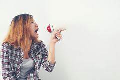 Young hipster woman shouting through megaphone. Young woman shouting through megaphone Stock Photography
