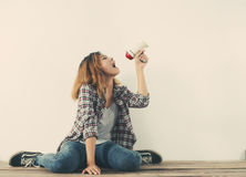 Young hipster woman shouting through megaphone. Young  woman shouting through megaphone Royalty Free Stock Images