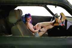 Young hipster woman sits in old rusty car Royalty Free Stock Photos