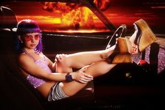 Young hipster woman sits in old rusty car against a nuclear apocalypse royalty free stock photos