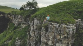 Young hipster woman is sitting on the edge on the grass of tall wall of rock. Aerial view. Drone is flying slow backward. From model. Establishing revealing stock footage