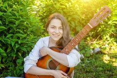 Young hipster woman sitting in grass and playing guitar on park or garden background. Teen girl learning to play song. And writing music. Hobby, lifestyle stock images