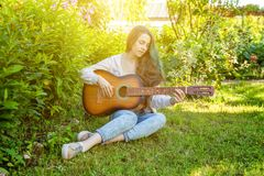 Young hipster woman sitting in grass and playing guitar on park or garden background. Teen girl learning to play song. And writing music. Hobby, lifestyle royalty free stock images