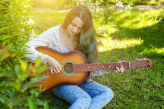 Young hipster woman sitting in grass and playing guitar on park or garden background. Teen girl learning to play song. And writing music. Hobby, lifestyle stock image