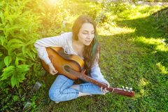 Young hipster woman sitting in grass and playing guitar on park or garden background. Teen girl learning to play song. And writing music. Hobby, lifestyle royalty free stock photo